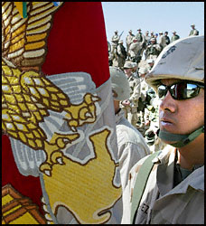 A Marine Corps color guard gathers with troops in the Kuwait desert. Photo taken February 6, 2003 (Reuters)